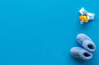 Frauenarztpraxis Marienheide Dr. Aleksandrow - Kinderwunschberatung - Kinderschuhe und Schnuller auf blauem Hintergrund